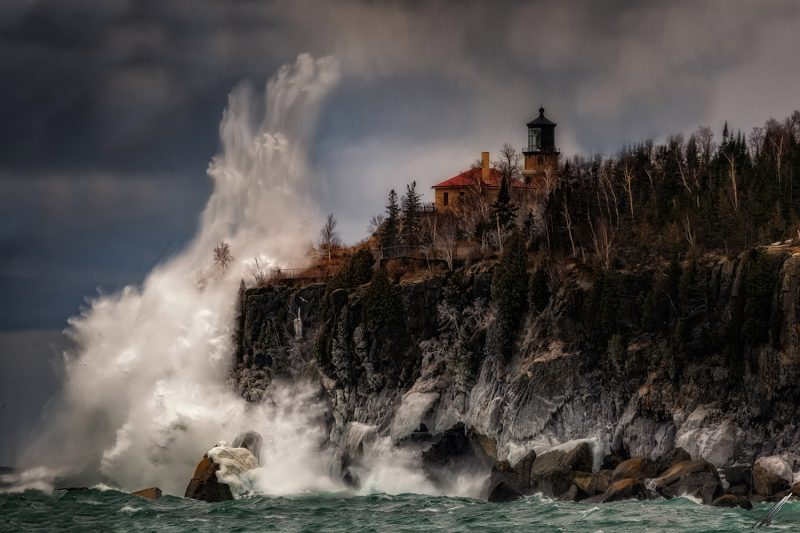 huge wave splashing against cliff with lighthouse