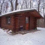 The log cabin looks warm amidst the snow in the winter