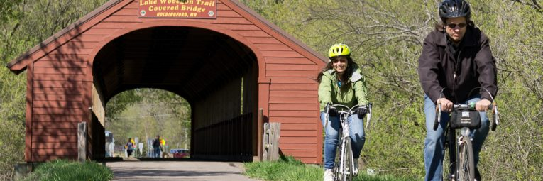 two happy bikers emerge from the covered bridge
