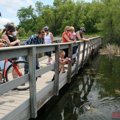 a kid fishes from the bridge while cyclists take a break to watch