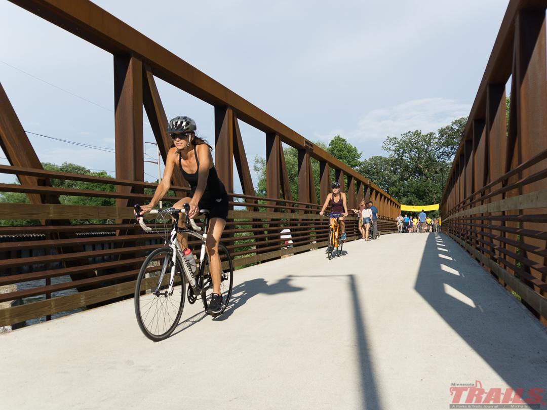 a few bikers cross a bridge