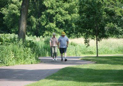 An older couple ambles down the paved bike trail