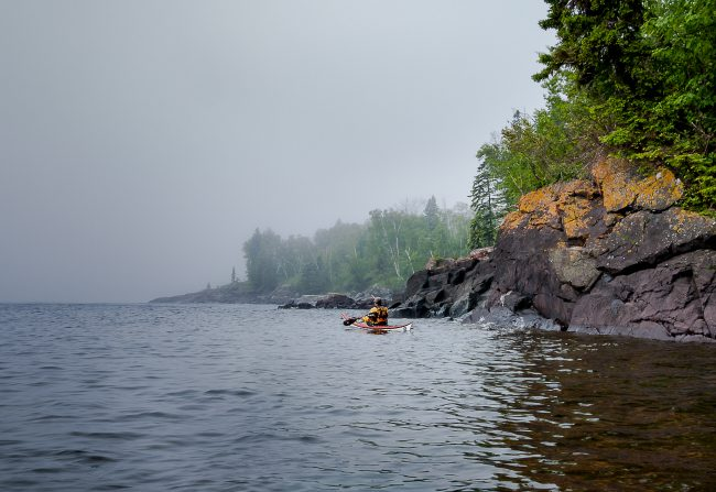kayaker in Lake Superior by rocky shore
