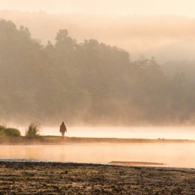 Silhouette of woman walking on misty shore of St. Croix River
