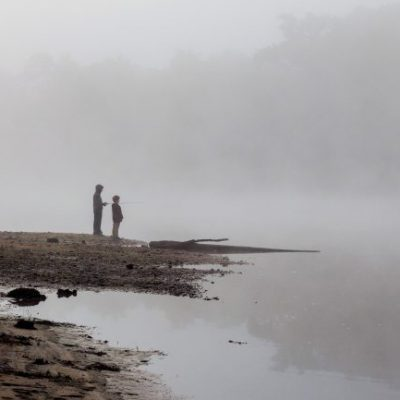Two boys fishing from shore on misty St. Croix River