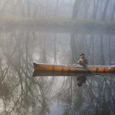 Older man canoeing in misty St. Croix River