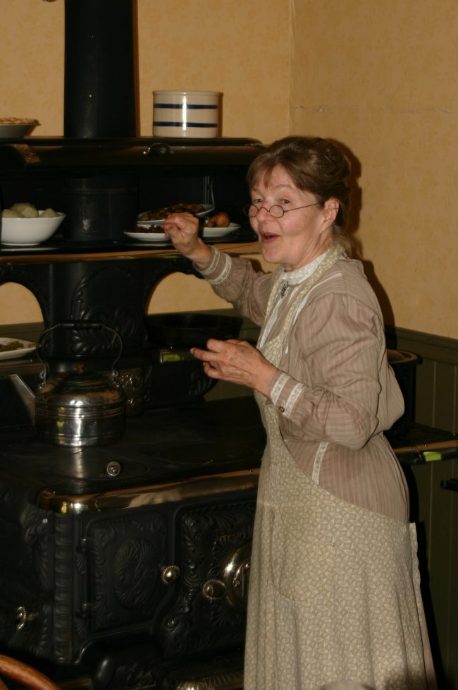 woman in settler clothes at stove